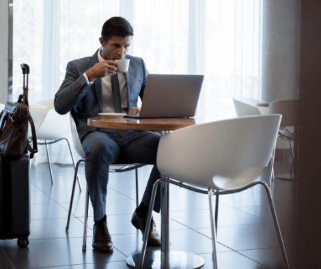 man in suit drinking coffee at table with laptop