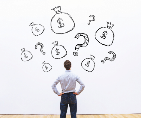 man standing in front of whiteboard with question marks and money bags