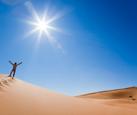 person standing on sand hill in sunny weather