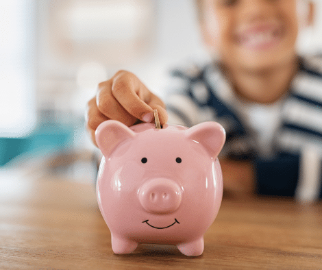 kid putting coins into piggy bank