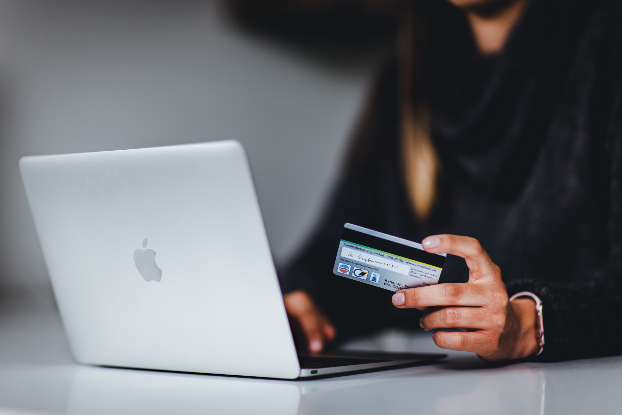 woman on laptop with credit card in hand