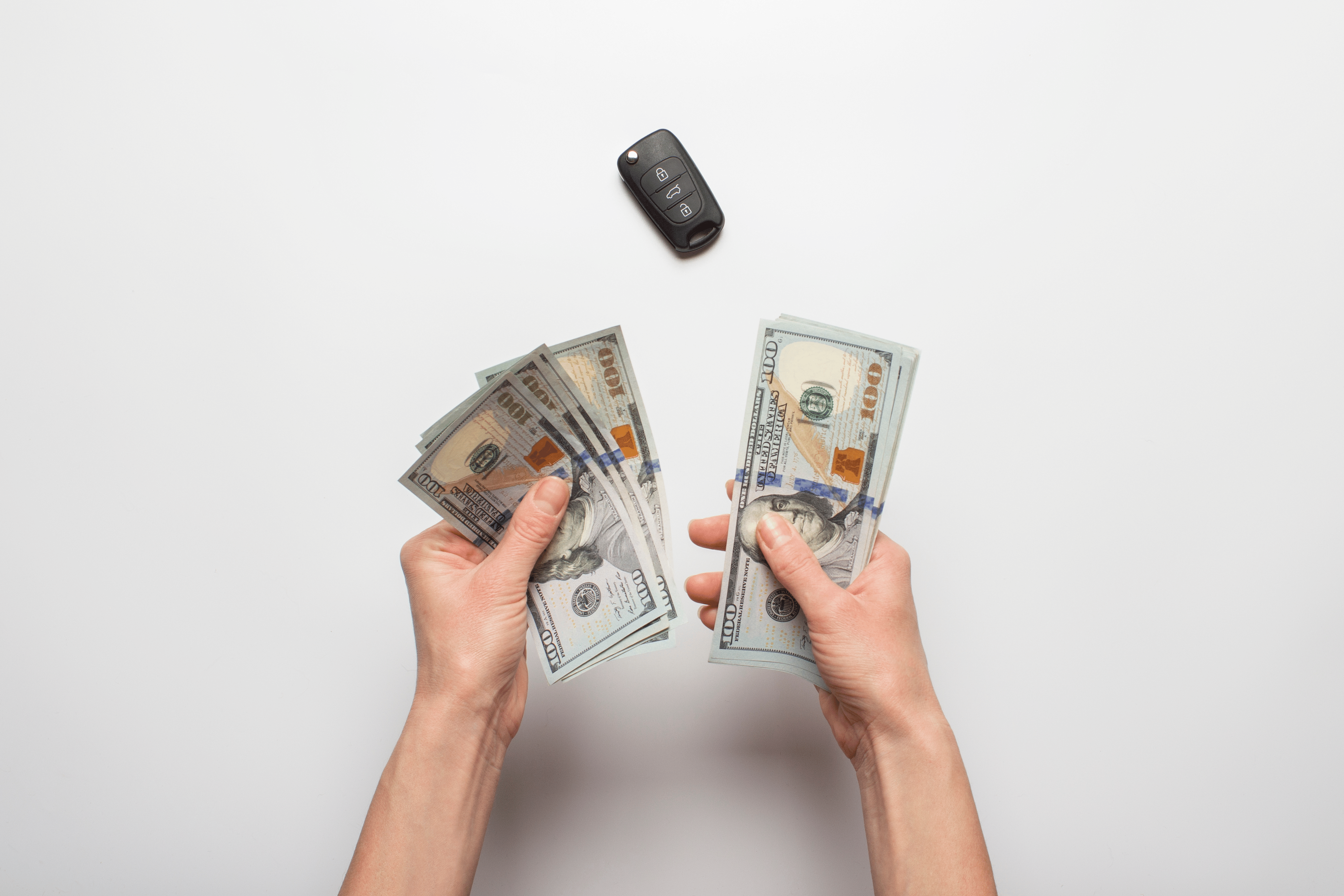 woman holding money with car keys on table